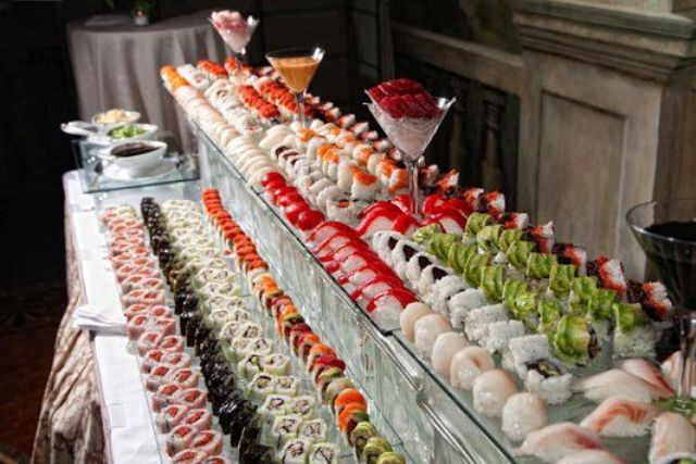 a large sushi bar with food displayed on glass shelves and sauces on a glass stand