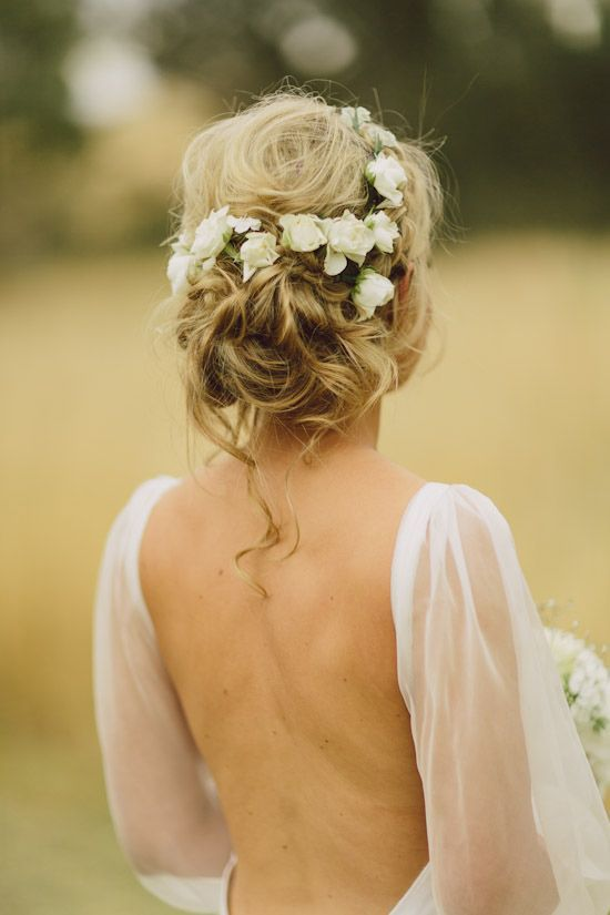 a messy updo with white flowers tucked in looks very summer-like