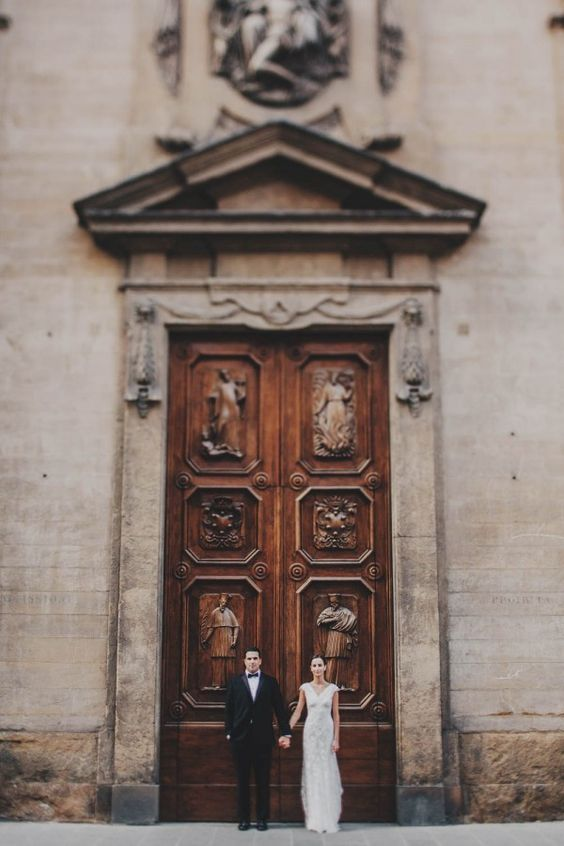 an antique church and a happy couple next to the doors