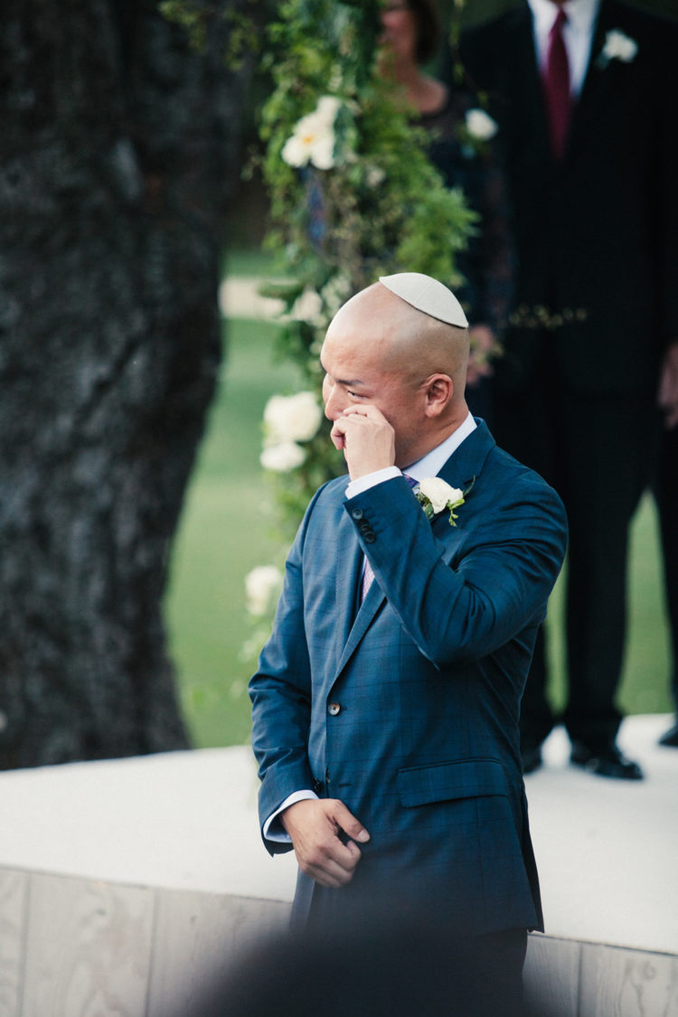 The groom was wearing a windowpane blue suit, a pink tie and a traditional Jewish kippah