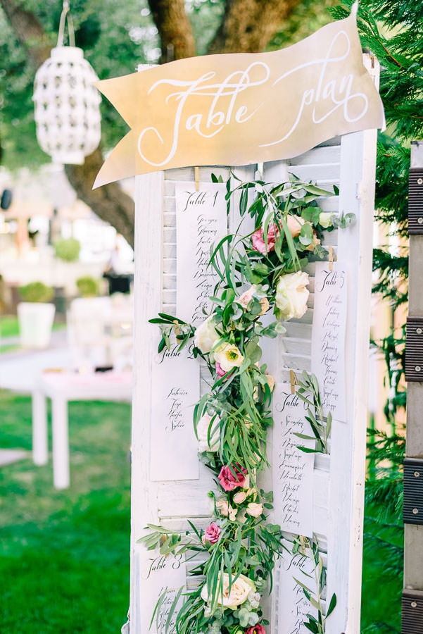 The seating chart made of old shutters and decorated with flowers and greenery