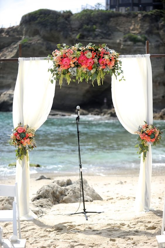 a wWood wedding arch with draping fabric and flowers in peach and coral