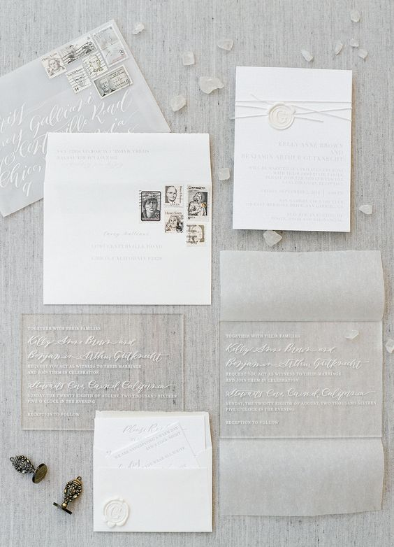 white and grey wedding invitation suite with an elegant script on clear acrylic invitation