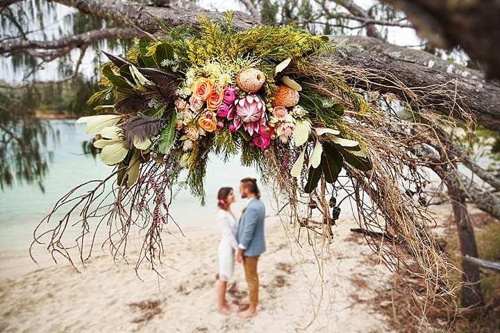 A fallen tree was decorated with bold flowers, leaves and feathers and it was used instead a wedding arch