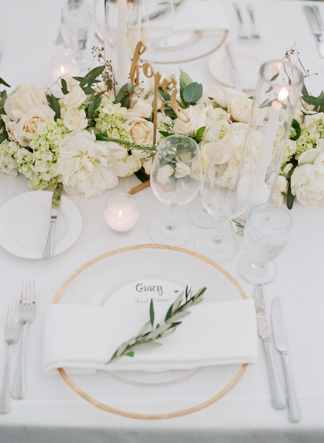 Gold table numbers, platters and candles make this table setting gorgeous