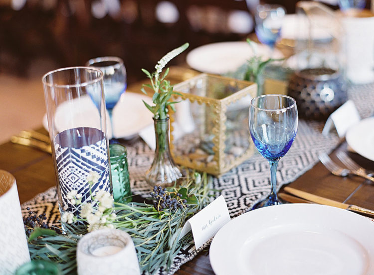 The wedding tablescapes were decorated with textile table runners, glass vases, candle holders, air plants and greenery