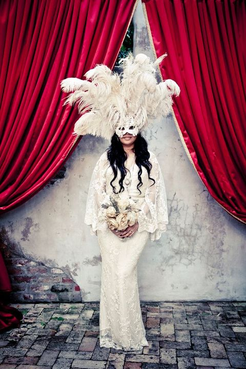 an oversized feather mask for a Mardi Gras bride