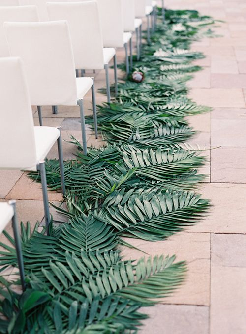 minimalist white chairs and palm leaves on the floor