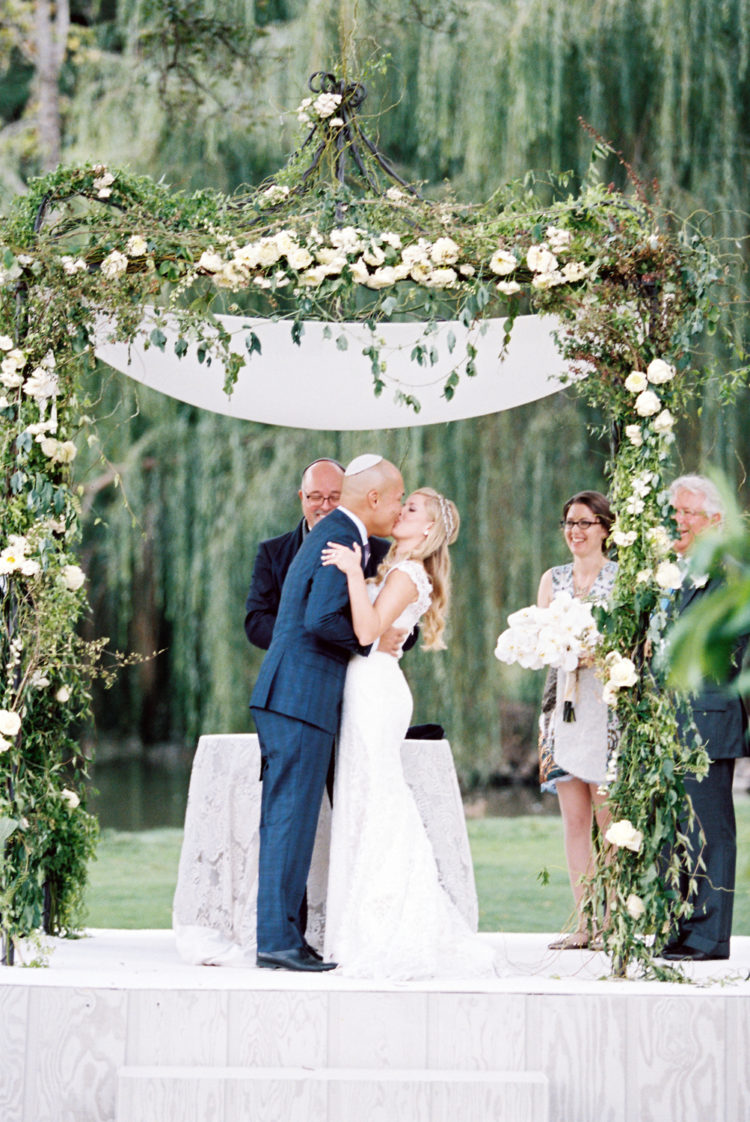 the wedding chuppah looked perfectly elegant with greenery and white flower decor