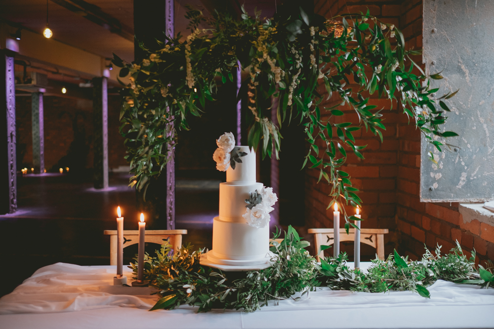 the wedidng cake was put in front of the window, styled with greenery on the table and over the cake too