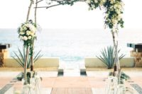 08 wooden arch with lush ivory florals by the beach