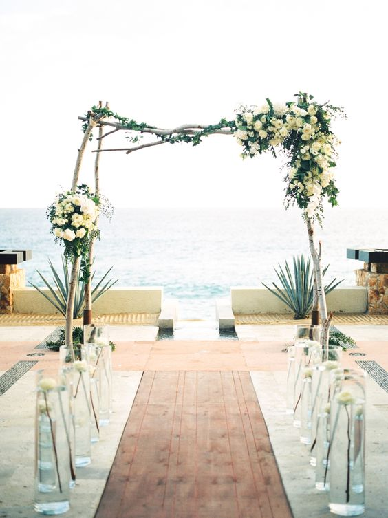 wooden arch with lush ivory florals by the beach