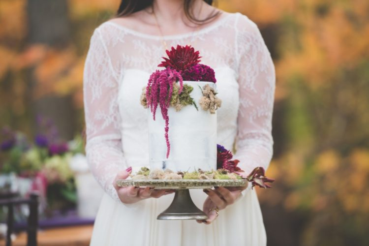The woodland-themed wedding cake decorated with moss and bold florals