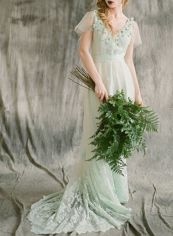 a light green wedding dress decorated with fabric leaves and a greenery wedding bouquet