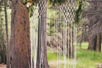 09 hanging macrame backdrop with flowers looks ethereal