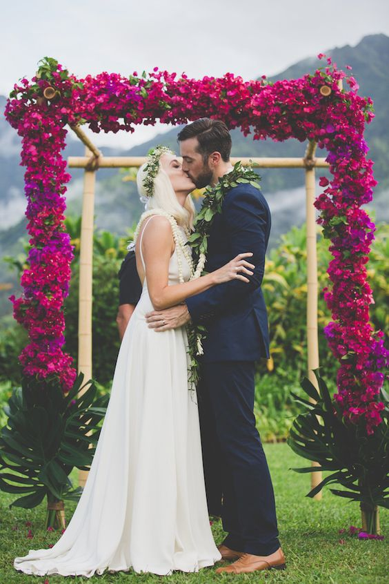 very bold hot pink flower wedding arch for a tropical wedding