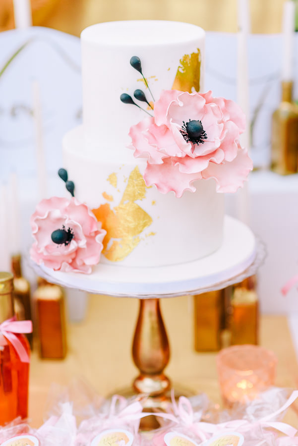 The wedding cake decorated with gold touches and pink flowers