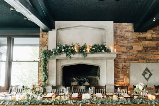 The wedding tablescape was decorated with eucalyptus, candles and a fireplace added coziness
