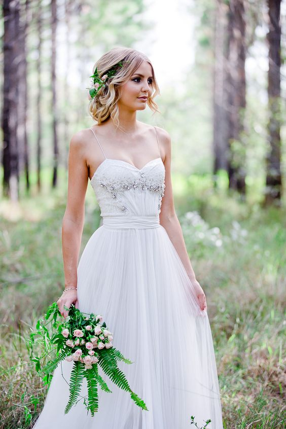 a white wedding dress on spaghetti straps with a rhinestone bodice and a leaf and floral crown