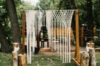 10 boho wedding arch with a macrame hanging, an embroidered rug and wooden logs
