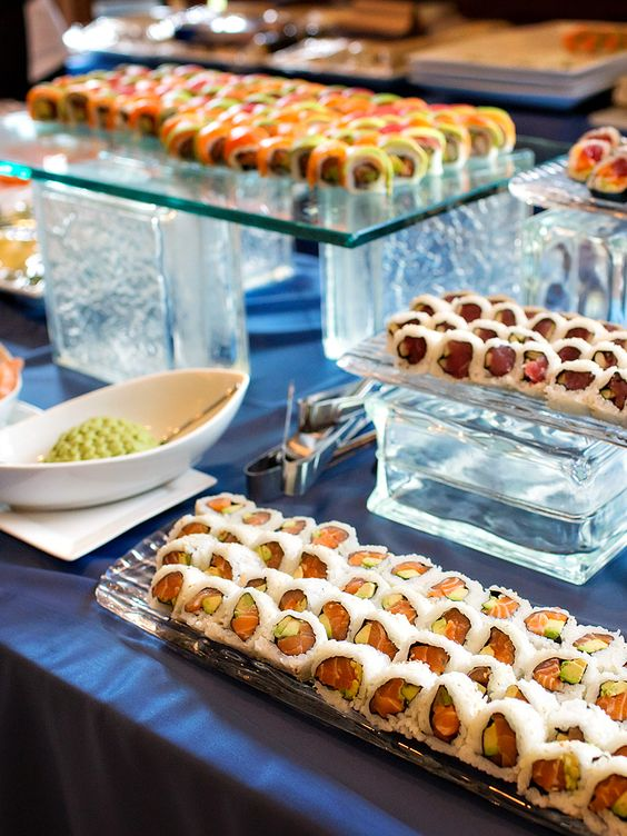 glass stands with various types of sushi and bowls with sauces