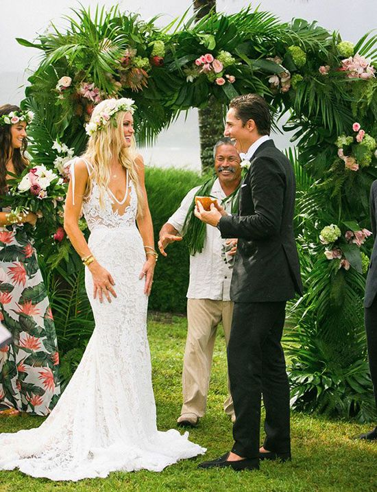 lush wedding arch fully covered with palm leaves and peach flowers