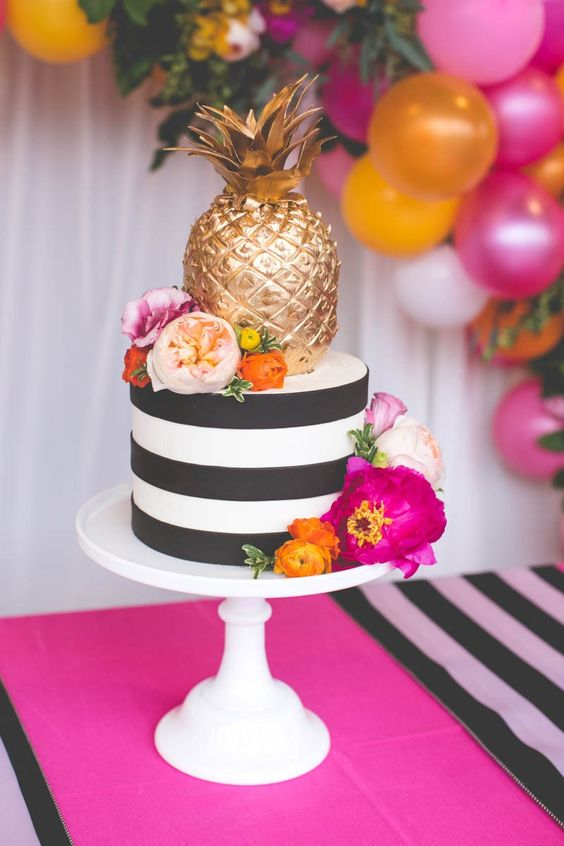 striped wedding cake with bold blooms and a gilded pineapple
