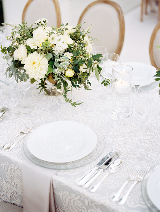 The centerpieces were done of white flowers and greenery, and the lace tablecloths were super delicate and chic