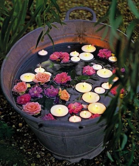 a galvanized bathtub with floating candles and flowers for a rustic touch