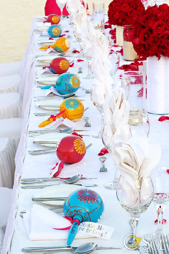 all-white tablescape with red roses and maracas to embrace the destination