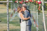 12 birch branch wedding arch with bold flowers and a macrame hanging