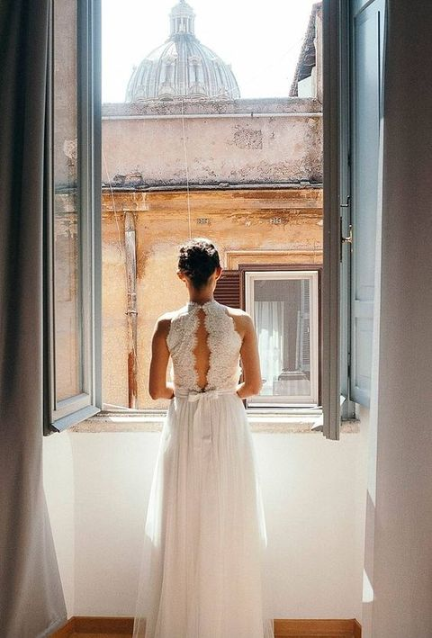 such a cool photo of the bride by the window with some Rome sites is a must