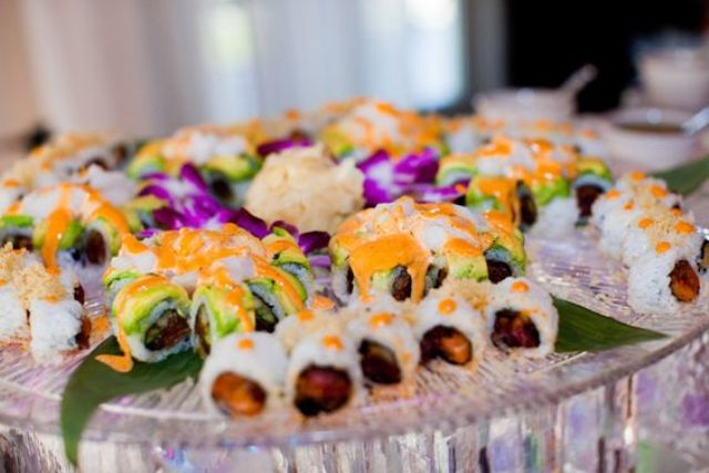 sushi on glass plates with tropical flowers and leaves