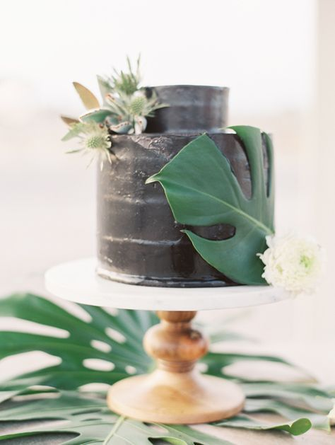 black wedding cake with a palm leaf and thistle