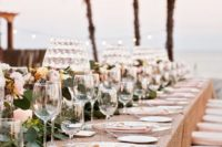 13 glam table setting with a sequin tablecloth, a floral garland and candles