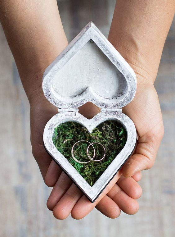 whitewashed heart shaped wedding ring box filled with moss