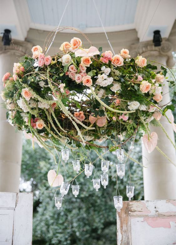 a grapevine flower chandelier in pink and peachy, with hanging candle holders