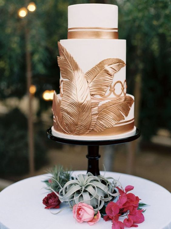 white cake decorated with copper edible palm leaves and stripes