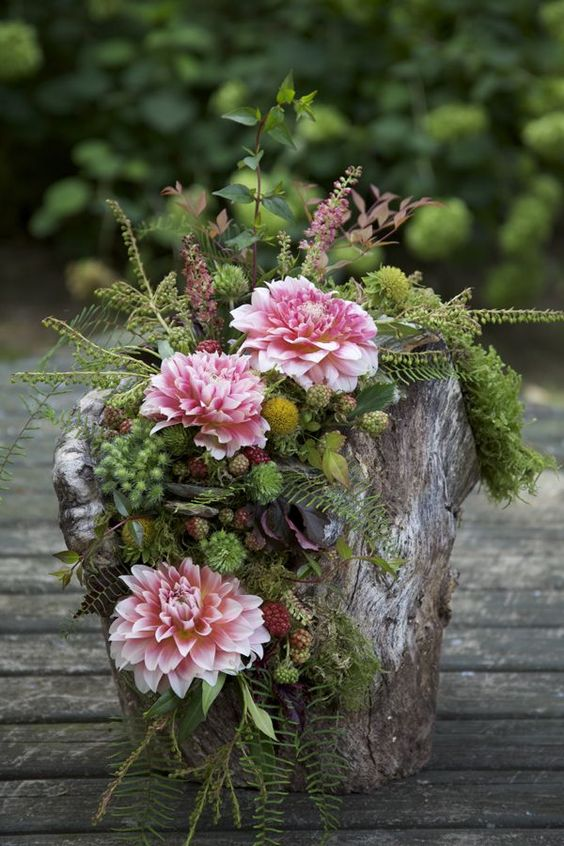 a wooden log with greenery, moss, flowers and berries