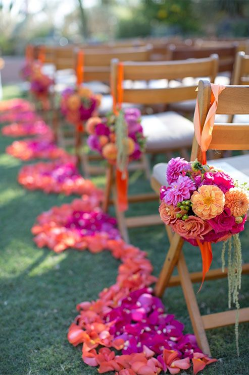 bold orange and pink blooms make for a dramatic aisle