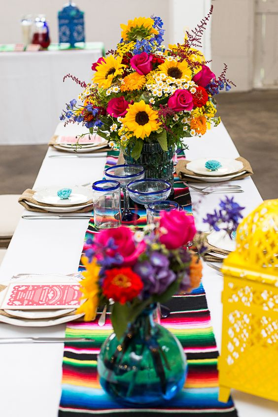 Mexican-themed table setting with a striped runner and bold florals