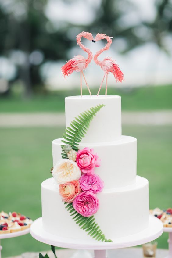 a plain white cake decorated with flowers and leaves and with a flamingo cake topper