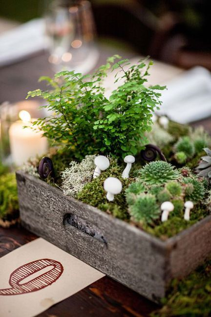 a woodland centerpiece in a crate with moss, succulents, greenery and faux mushrooms