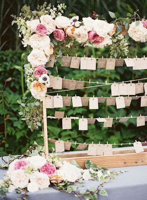 escort cards on strings and frame decorated with lush florals