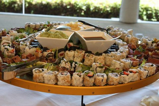 rich sushi bar on a wooden plate with sauce bowls in the center