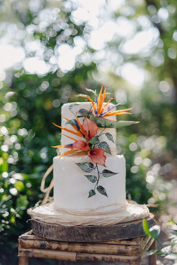 a simple cake with tropical flowers and greenery decor