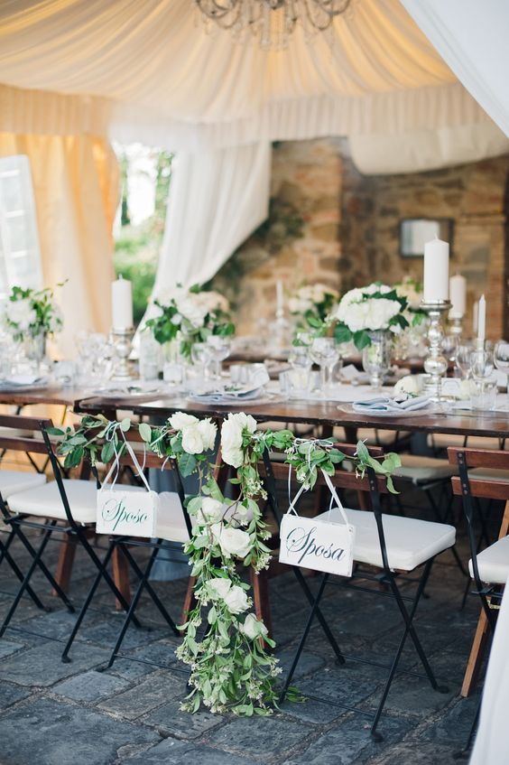 chic table and chair decor with greenery and white flowers