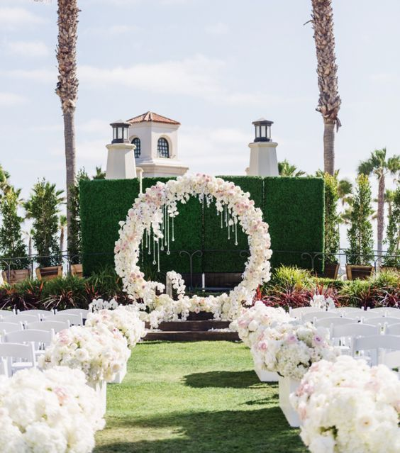 lush white flower aisle decor and a circle white flower arch with crystals