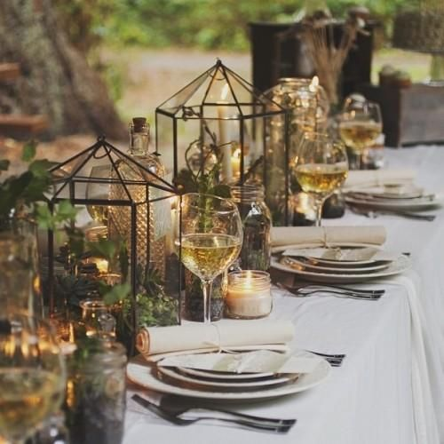 tablescape with greenery in lanterns, candles and a white tablecloth