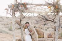 18 whitewashed wooden chuppah with a macrame hanging above, feathers and flowers